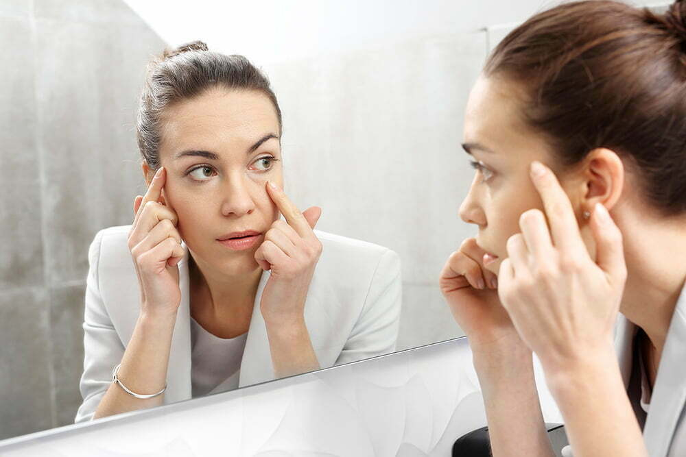 woman looking in mirror examining upper and lower eyelids